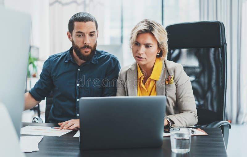 Professionnels d'affaires aux moments fonctionnants Groupe de jeunes coworking sûrs à l'aide de l'ordinateur tandis que temps de  photo stock