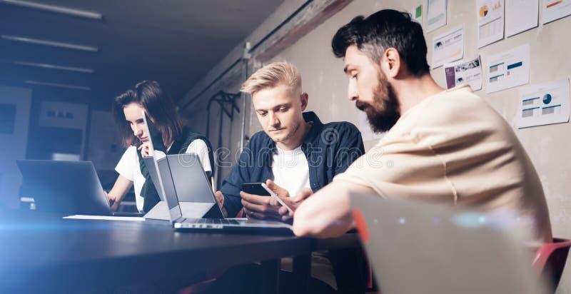 Professionnels d'affaires aux moments fonctionnants Groupe de jeunes coworking sûrs analysant des données utilisant le moment d'o photographie stock libre de droits