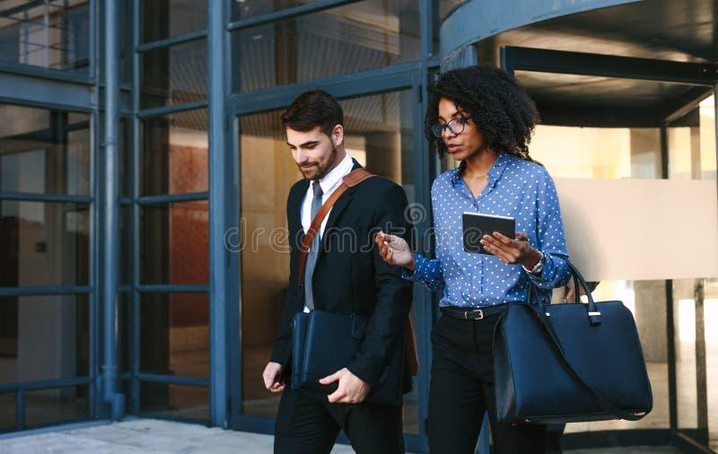 Professionnels d'entreprise constituée en société marchant hors de l'immeuble de bureaux images stock