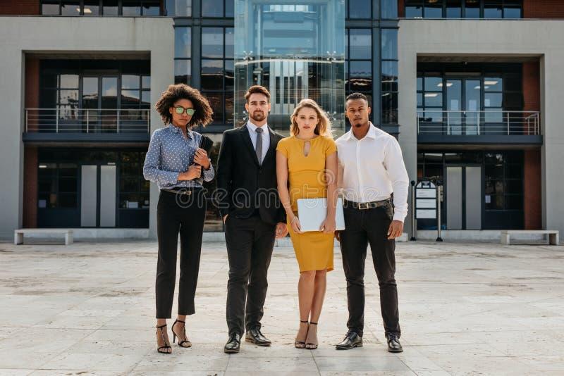 Professionnels d'entreprise dans l'avant un immeuble de bureaux moderne photographie stock