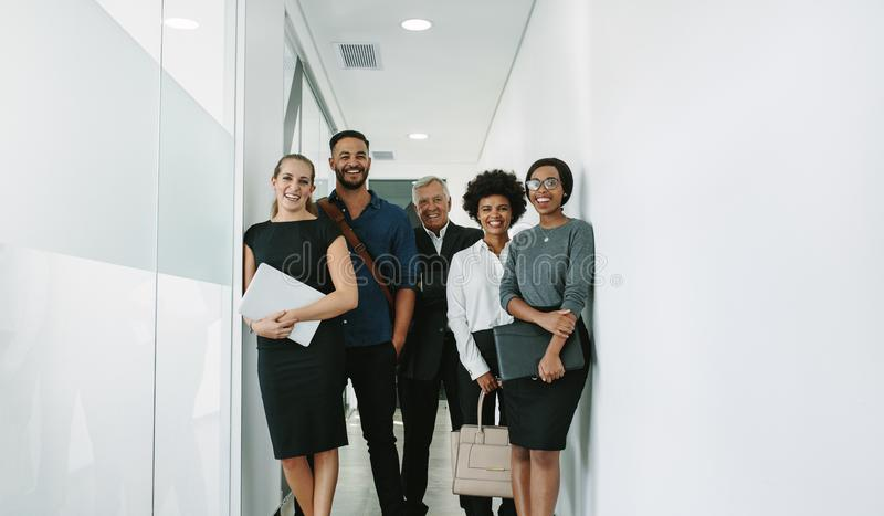Professionnels d'entreprise multiraciaux dans le couloir de bureau photo stock