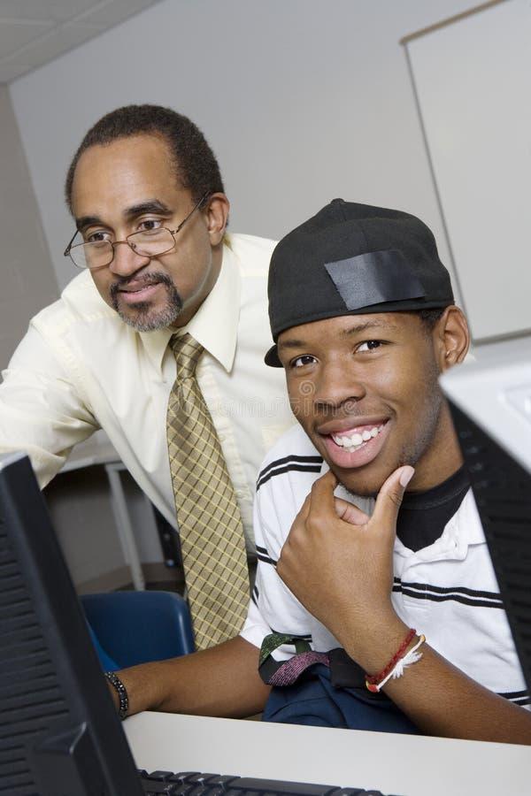 Professor alto Helping Student imagem de stock