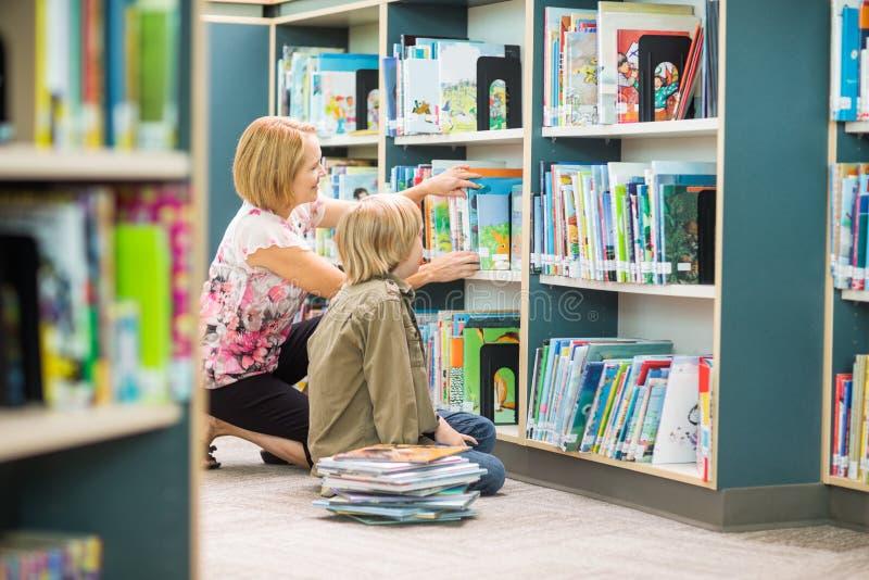 Professor Assisting Boy In que seleciona livros dentro imagens de stock