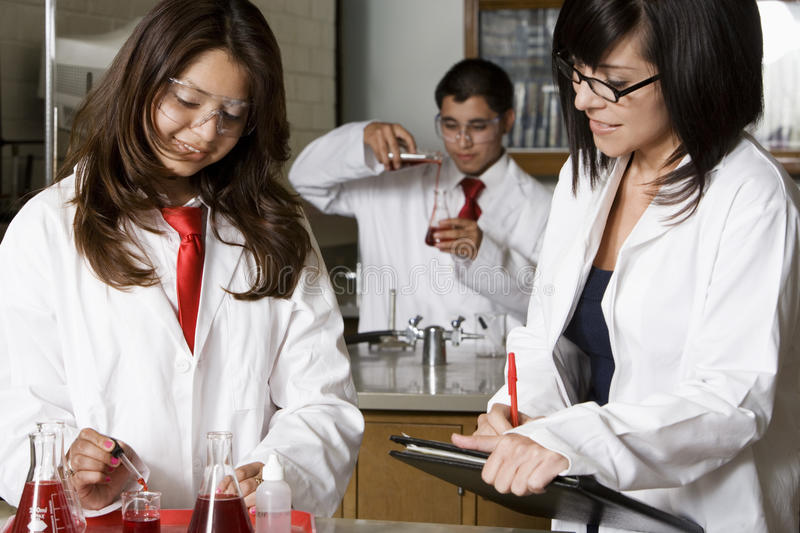 Professor Assisting High School Students In Science Lab. Female professor assisting high school students in chemistry lab stock photography