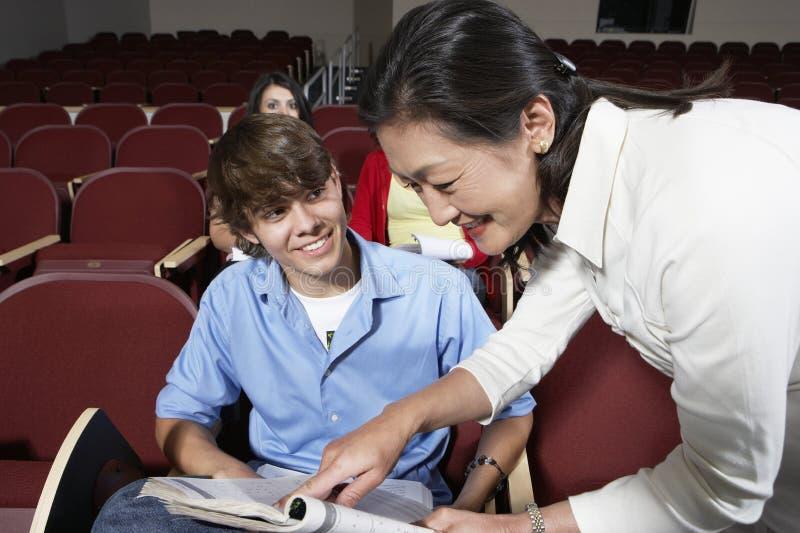 Professor Assisting Male Student na sala de aula imagem de stock royalty free