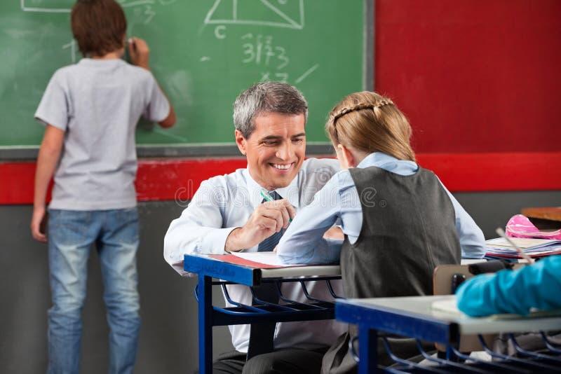 Download Professor Assisting Schoolgirl At Desk Stock Image - Image: 33272813