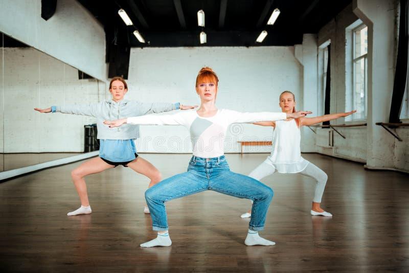 Professor bonito magro do bailado que faz squatting com os dois estudantes novos imagens de stock royalty free