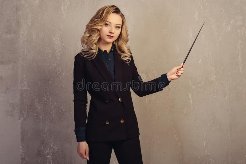 Professor bonito novo da mulher com ponteiro à disposição perto de uma parede textured cinzenta fotos de stock