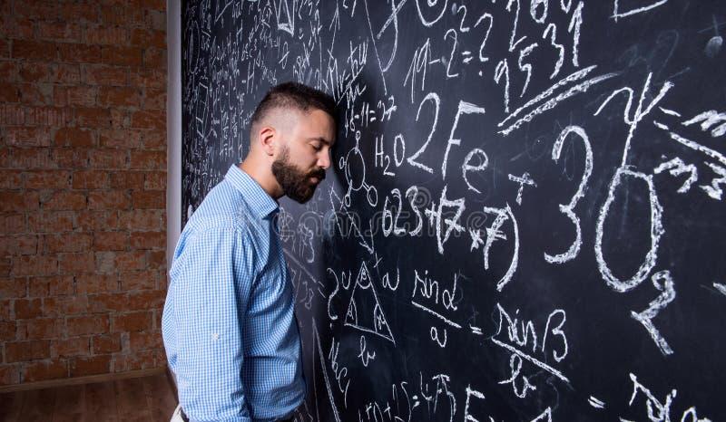Professor cansado que dorme contra o quadro-negro grande com matemático foto de stock