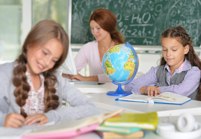 Professor com as duas meninas na lição foto de stock