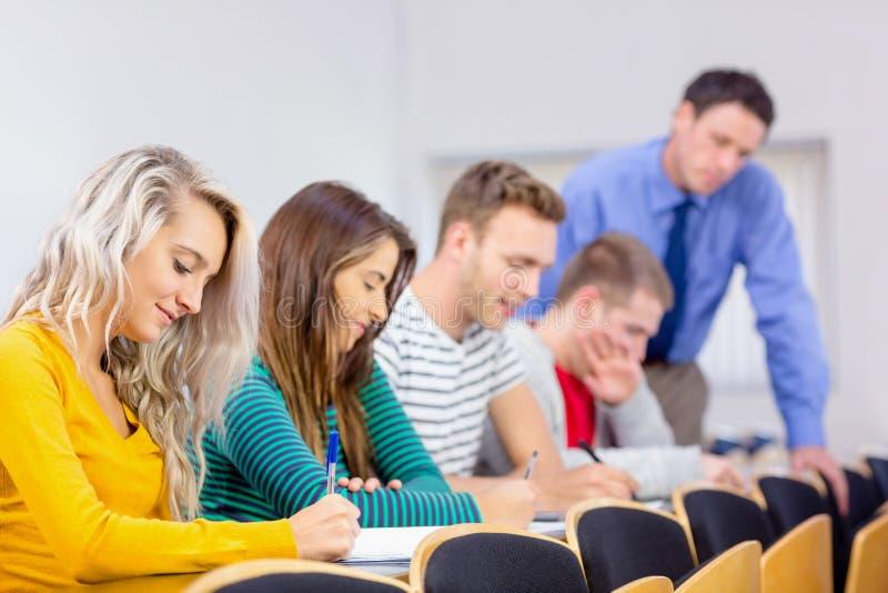 Professor com as estudantes universitário na sala de aula imagens de stock royalty free