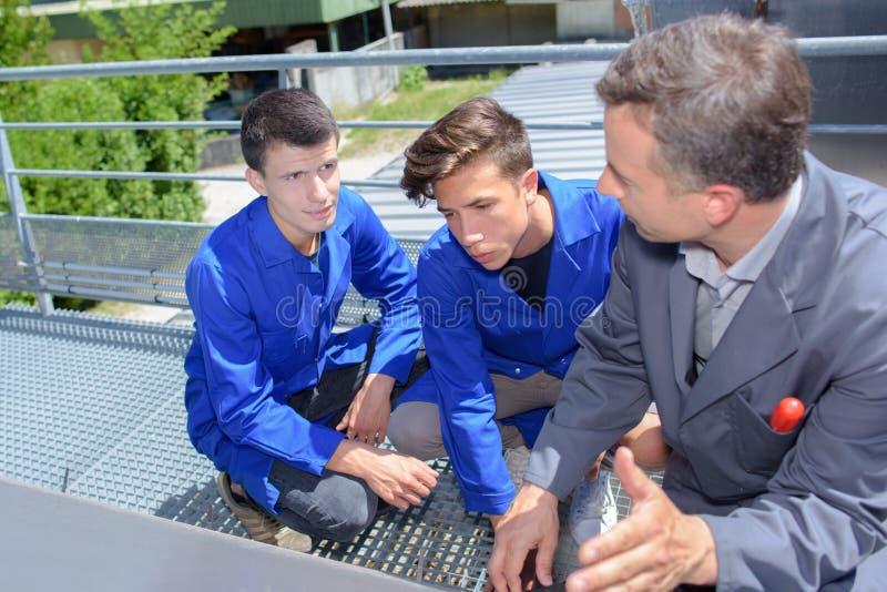 Professor com estudantes fora na plataforma do metal imagem de stock