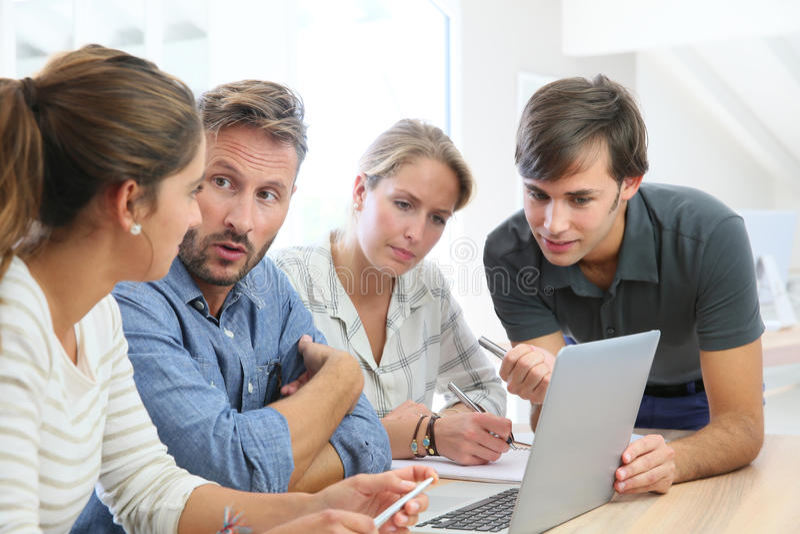 Professor com grupo de estudantes na classe que trabalha no portátil fotos de stock