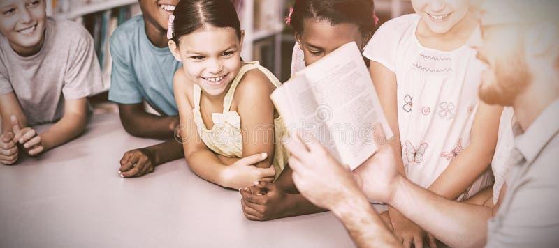 Professor com os estudantes de ensino do livro na biblioteca imagens de stock royalty free