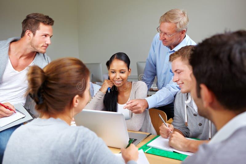 Professor com os estudantes na faculdade imagem de stock royalty free