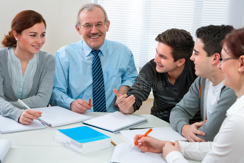 Professor com os estudantes na sala de aula foto de stock