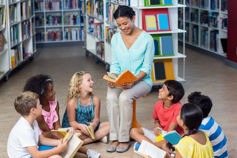 Professor com os livros de leitura dos estudantes fotos de stock royalty free