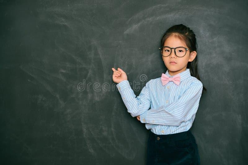 Professor consideravelmente pequeno irritado que aponta o quadro-negro imagens de stock royalty free