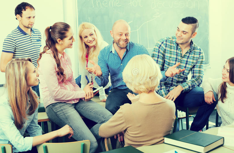 Professor consulting different age students royalty free stock photo