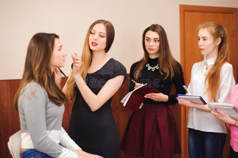 Professor da composição com suas meninas do estudante Lição tutorial da composição na escola da beleza Classe mestra da composiçã fotografia de stock