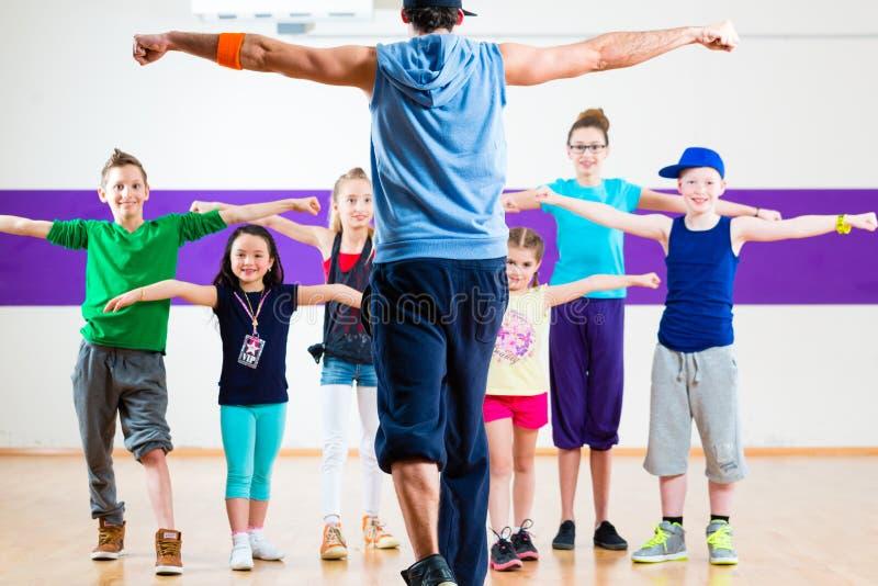Professor da dança que dá a crianças a classe da aptidão de Zumba fotografia de stock