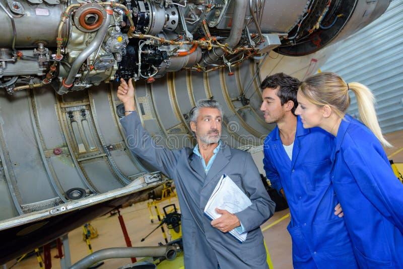 Professor da engenharia que verifica os motores do avião com os estudantes fotos de stock