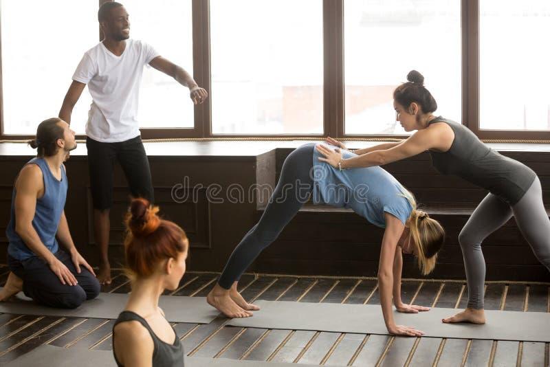 Professor da ioga que ajuda à mulher que faz para baixo - enfrentar o stretchin do cão foto de stock