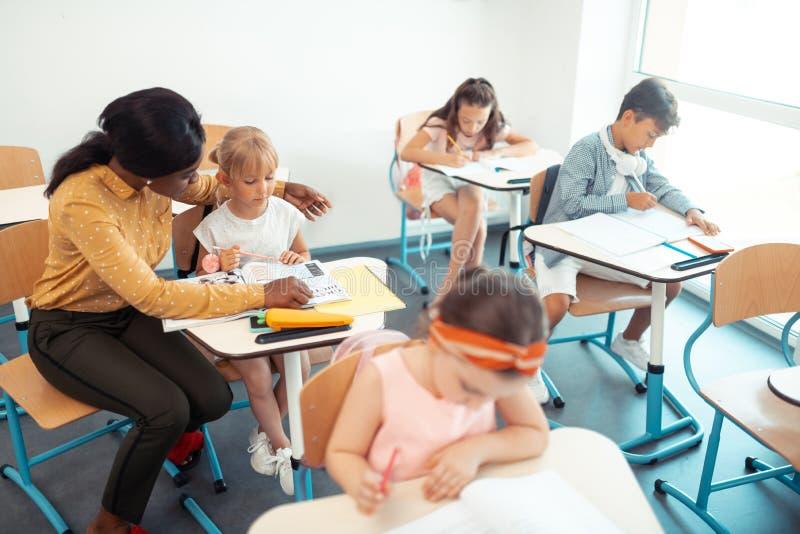 Professor de cabelo escuro que senta-se perto de seus alunos que ajudam os com tarefa fotografia de stock royalty free