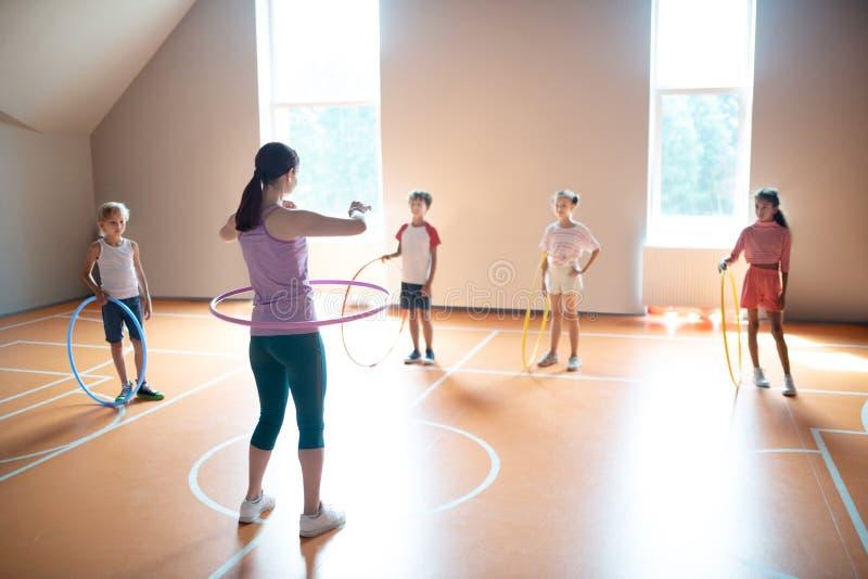 Professor de educação física usando leggings ensinando crianças a usar hula-hoop fotos de stock royalty free