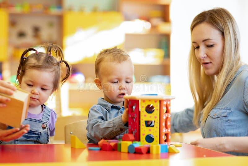 Professor de jardim de infância que joga com os bebês no berçário Brinquedos desenvolventes para o pré-escolar fotografia de stock royalty free