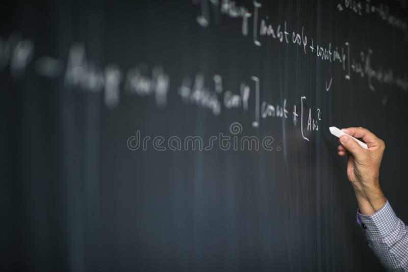 Professor de matemática pelo quadro-negro durante mathclass foto de stock
