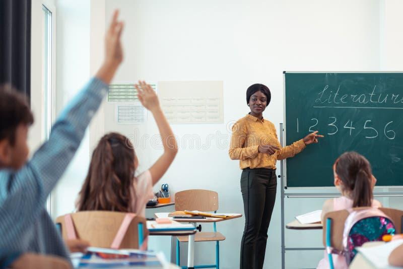 Professor de pele escura que dá a pergunta para seus alunos espertos imagem de stock