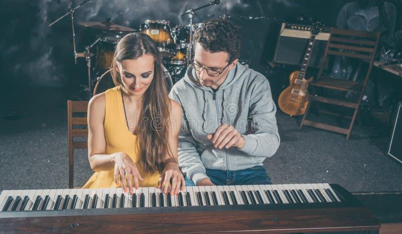 Professor de piano que dá lições de música a seu estudante fotos de stock