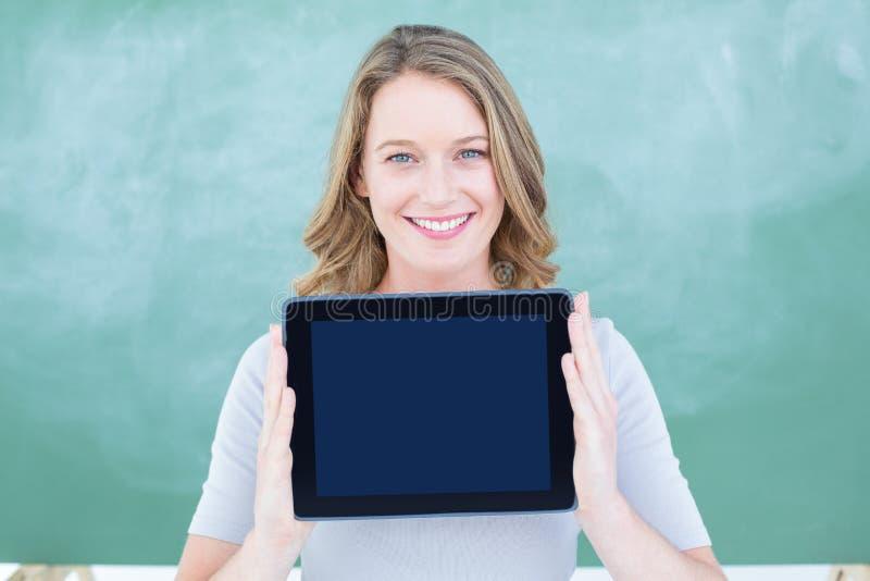 Professor de sorriso que guarda o PC da tabuleta na frente do quadro-negro fotos de stock