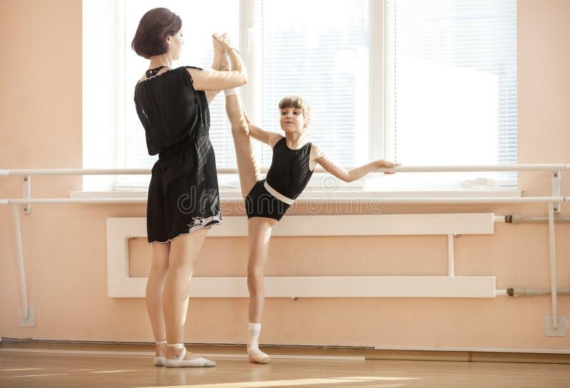 Professor do bailado que ajusta a posição do pé de bailarinas novas fotos de stock