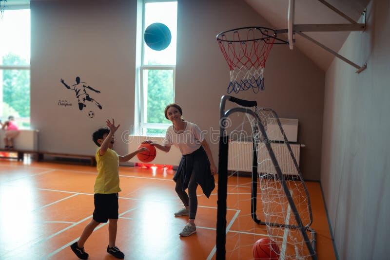 Professor dos esportes que joga o basquetebol com um dos alunos fotos de stock royalty free