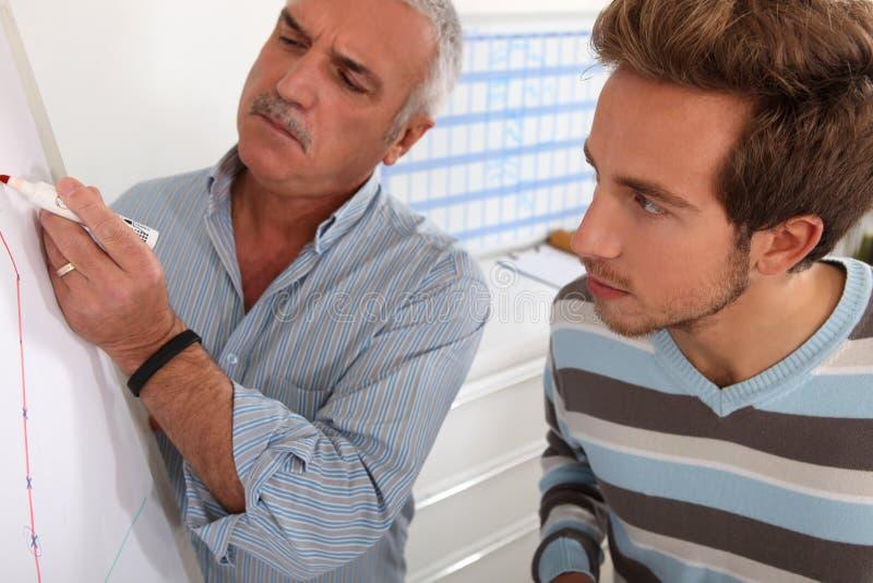 Professor e aluno que olham o gráfico imagens de stock