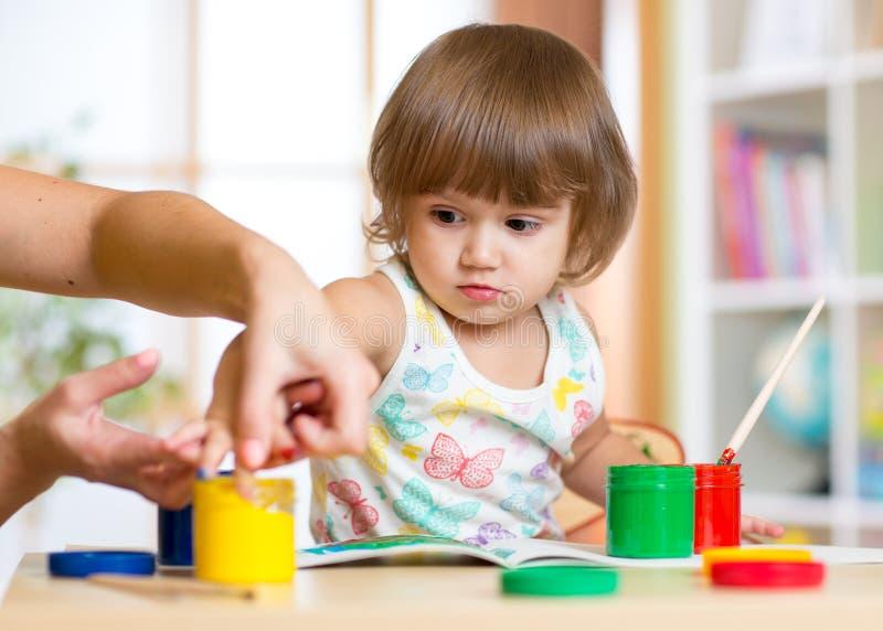 Professor e criança que pintam junto no berçário fotografia de stock