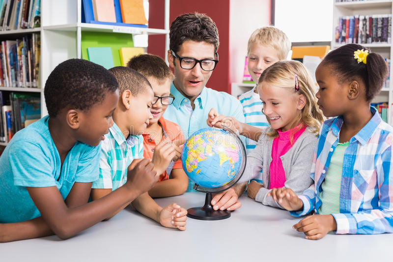 Professor e crianças que discutem o globo foto de stock