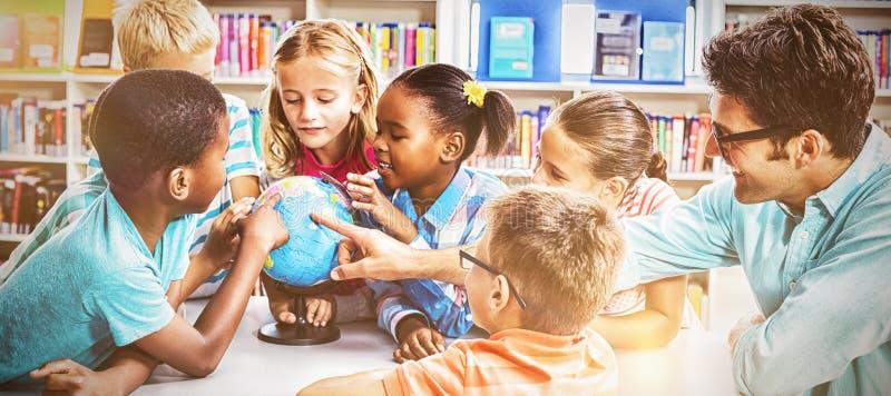 Professor e crianças que discutem o globo imagem de stock