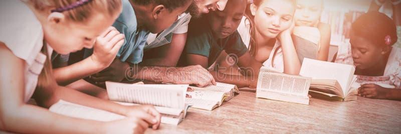 Professor e crianças que encontram-se no livro de leitura do assoalho na biblioteca foto de stock