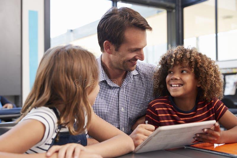 Professor e dois alunos na turma escolar que olha se fotografia de stock