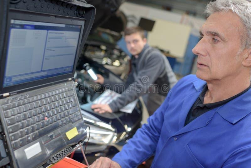Professor e estagiário do auto mecânico que executam testes na escola do mecânico imagem de stock royalty free