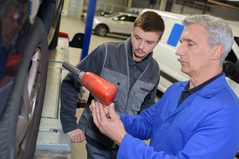 Professor e estagiário do auto mecânico que executam testes na escola do mecânico fotografia de stock