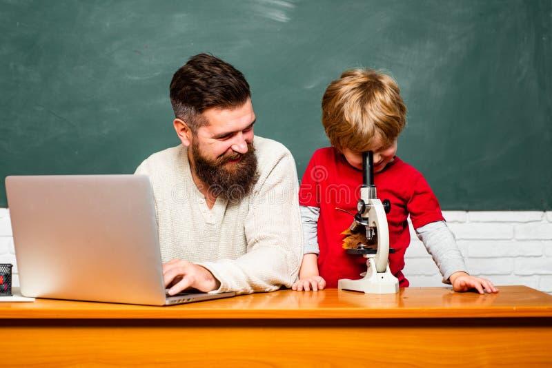Professor e estudante elementares na sala de aula Jogo do paizinho com estudante Professor e estudante que usa o portátil dentro imagem de stock royalty free