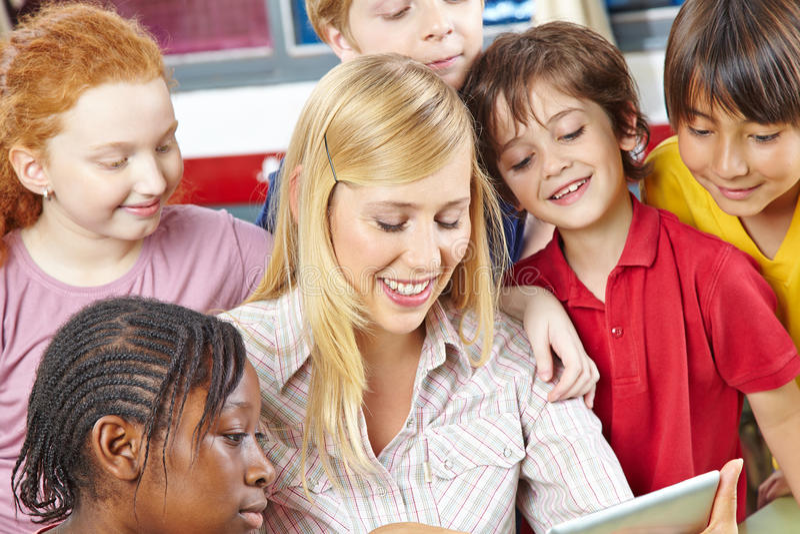 Professor e estudantes que olham o tablet pc imagem de stock royalty free