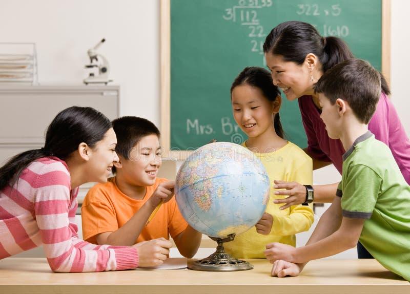 Professor e estudantes que vêem o globo na sala de aula fotografia de stock