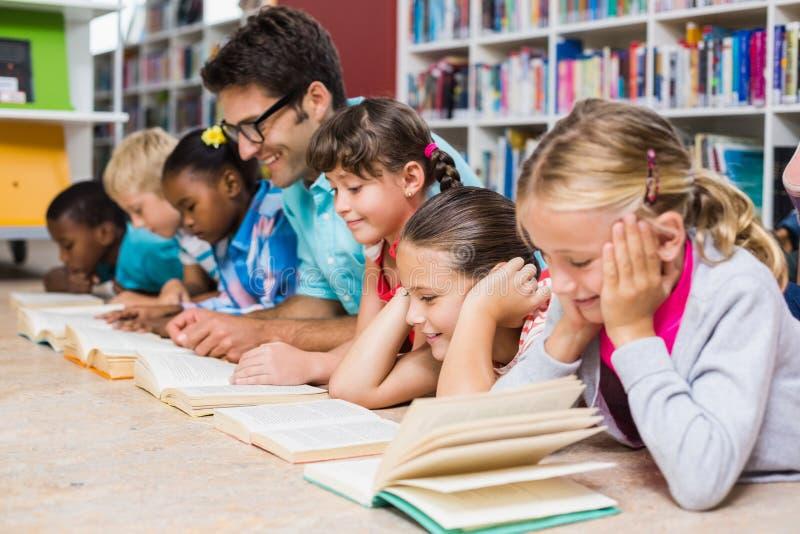 Professor e livro de leitura das crianças na biblioteca fotografia de stock royalty free