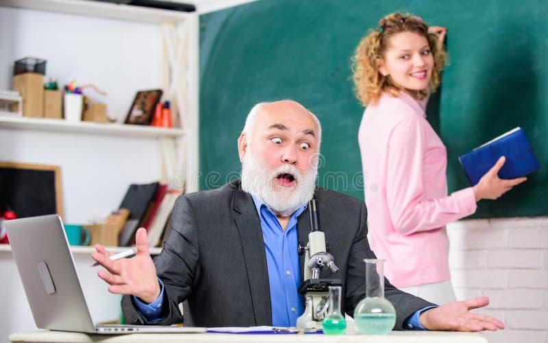 Professor e menina com o bloco de notas perto do quadro Educação da universidade da faculdade Biólogo ou químico com microscópio imagens de stock royalty free