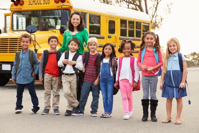 Professor e um grupo de crianças da escola primária em uma parada do ônibus fotos de stock
